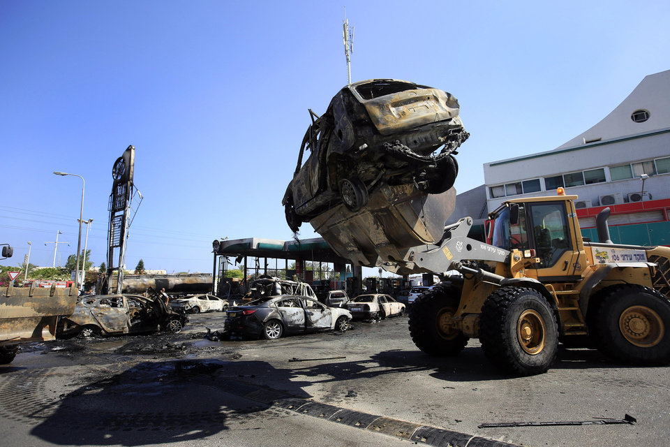 Photo - Destroyed cars are removed from a gas station that was hit by a rocket fired from the Gaza Strip in the city of Ashdod, Israel, Friday, July 11, 2014. The attack on the gas station in Ashdod looked to be the most serious attack in Israel in the four days of fighting that has seen Israel deliver a heavy blow to Gaza's Hamas leaders. The military have carried out more than 1,000 strike strikes against Gaza targets that have killed at least 95 people, including dozens of civilians. (AP Photo/Tsafrir Abayov)