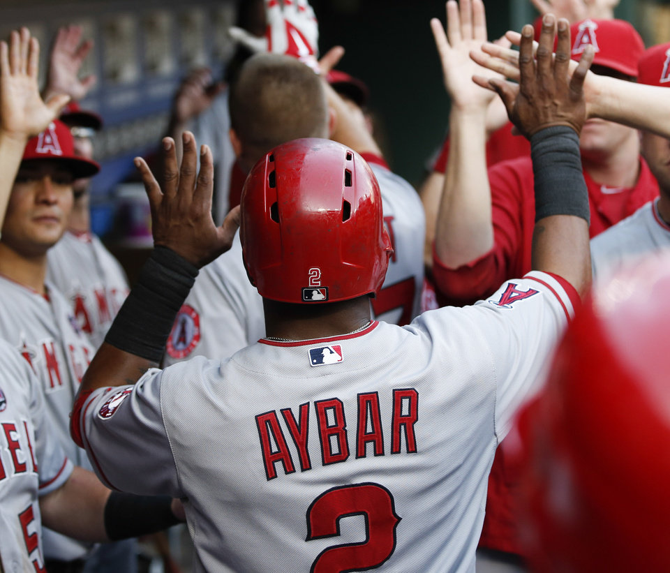 Photo - Los Angeles Angels' Erick Aybar (2) is congratulated by teammates after scoring a run against the Texas Rangers during the fifth inning of a baseball game, Monday, July 29, 2013, in Arlington, Texas. (AP Photo/Jim Cowsert)