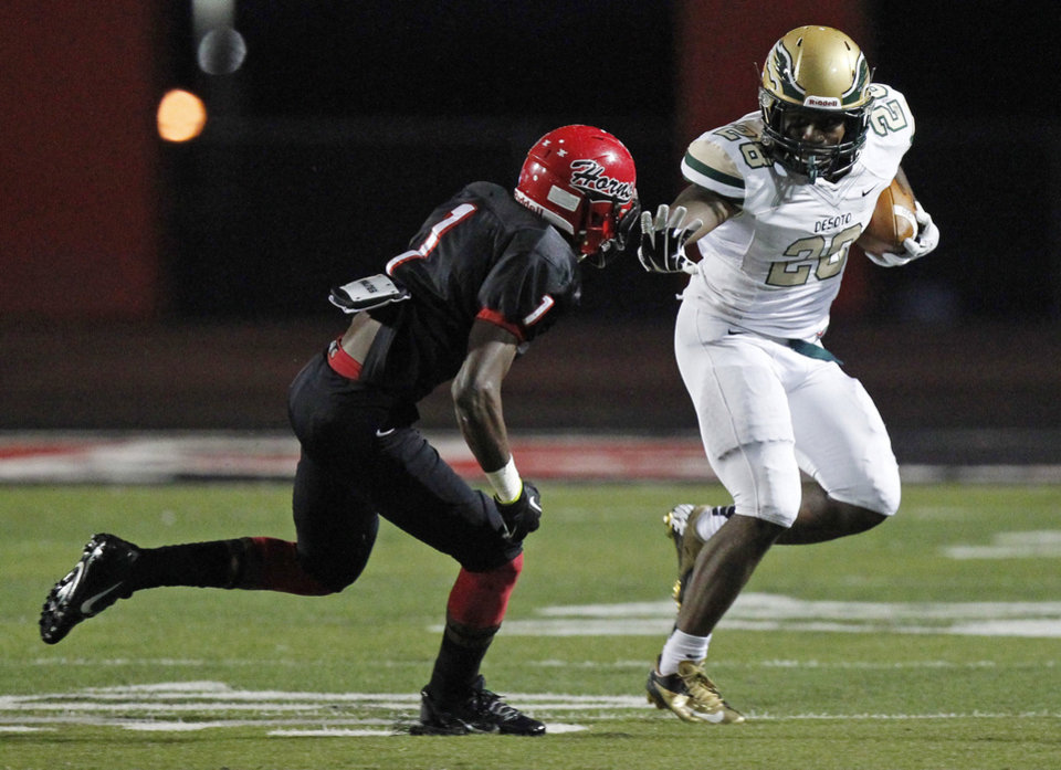 DeSoto running back Jatory Brown (28) prepares to stiff arm Cedar Hill defender Marcus Green (1) during their High School football game at Longhorns Stadium in Cedar Hill on September 20, 2013. PHOTO COURTESY DALLAS MORNING NEWS <strong>Michael Ainsworth</strong>