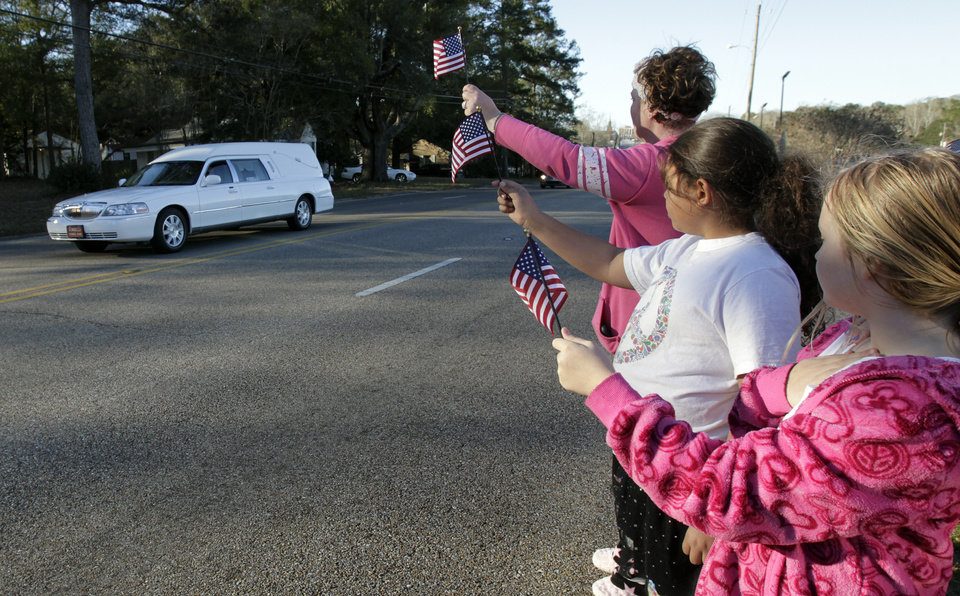 Photo - Gabriel Cavender, right, Kiya Buchanan, center, and Raechel Buchanan, left, hold up flags as the funeral procession for Charles