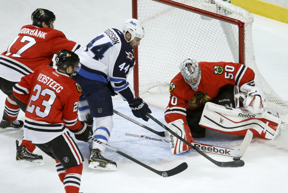 Photo - Chicago Blackhawks goalie Corey Crawford (50) makes a save on a shot by Winnipeg Jets defenseman Zach Bogosian (44) as Sheldon Brookbank (17) and Kris Versteeg (23) defend during the first period of an NHL hockey game Sunday, Jan. 26, 2014, in Chicago. (AP Photo/Charlie Arbogast)