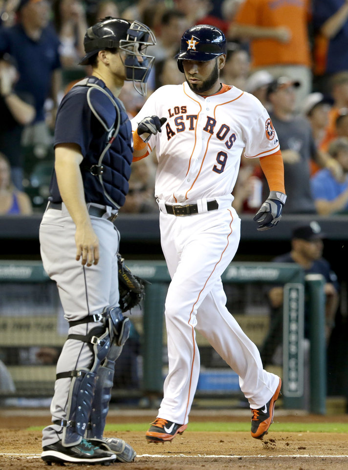 Photo - Houston Astros' Marwin Gonzalez (9) comes across home plate to score behind Seattle Mariners catcher Mike Zunino in the third inning of a baseball game on Saturday, May 3, 2014, in Houston. (AP Photo/Pat Sullivan)