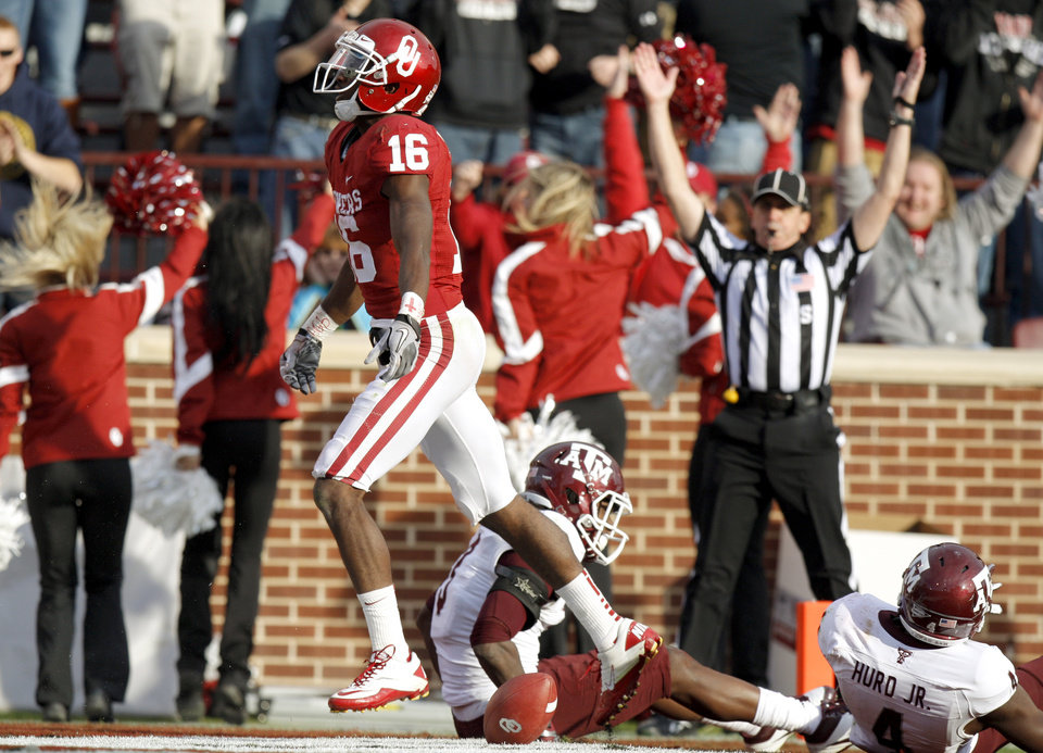 Photo - Oklahoma's Jaz Reynolds (16) celebrates a touchdown in front of Texas A&M's Lionel Smith (3) and Texas A&M's Toney Hurd Jr. (4) during the college football game between the Texas A&M Aggies and the University of Oklahoma Sooners (OU) at Gaylord Family-Oklahoma Memorial Stadium on Saturday, Nov. 5, 2011, in Norman, Okla. Oklahoma won 41-25. Photo by Bryan Terry, The Oklahoman