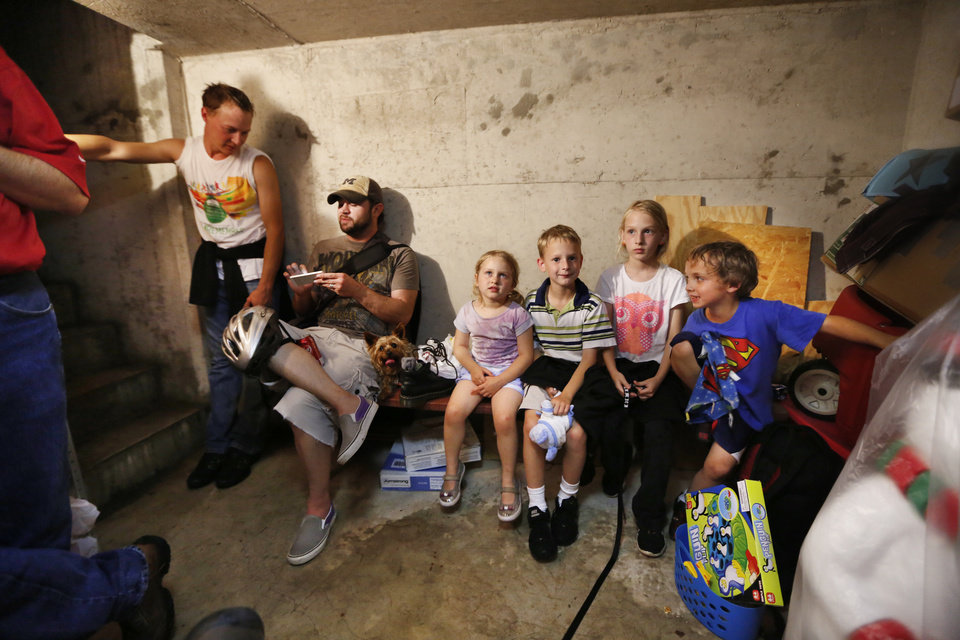 Kerry Melott, left, Jeff Short, ride out tornado warnings with their children Tori Short, 4yr, Nate Melott, 7yr, Natalie Melott, 10yr and Andrick Short, 7yr, in a storm shelter in NW Oklahoma City , Friday May 31, 2013.Photo By Steve Gooch, The Oklahoman