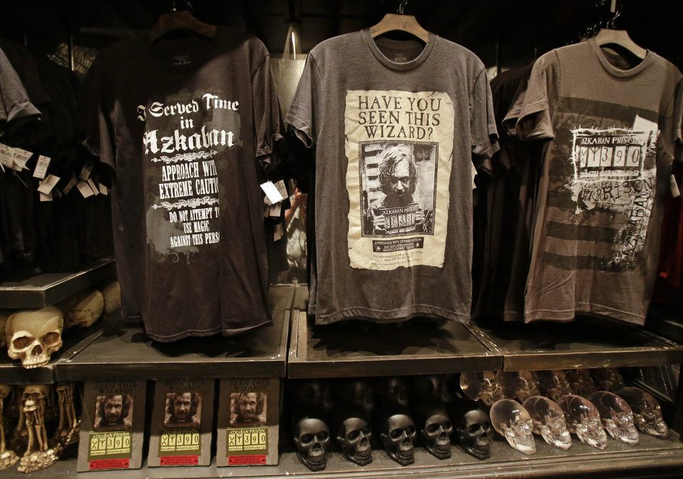 Photo - T-shirts and ceramic skulls are displayed at Borgin and Burkes in Knockturn Alley during a preview of Diagon Alley at the Wizarding World of Harry Potter at Universal Orlando, Thursday, June 19, 2014, in Orlando, Fla. (AP Photo/John Raoux)