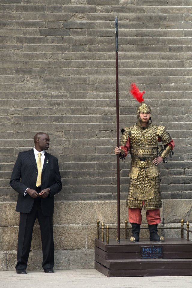 Photo - A U.S. secret service officer checks a Chinese performer dressed as an ancient warrior as U.S. first lady Michelle Obama visits a nearby city wall in Xi'an, in northwestern China's Shaanxi province, Monday, March 24, 2014. (AP Photo/Alexander F. Yuan)