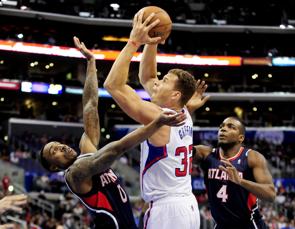Photo - Double-teamed by Atlanta Hawks guard Jeff Teague (0) and forward Paul Millsap (4), Los Angeles Clippers forward Blake Griffin (32) takes a shot in the first half of an NBA basketball game, Saturday, March 8, 2014, in Los Angeles. (AP Photo/Gus Ruelas)
