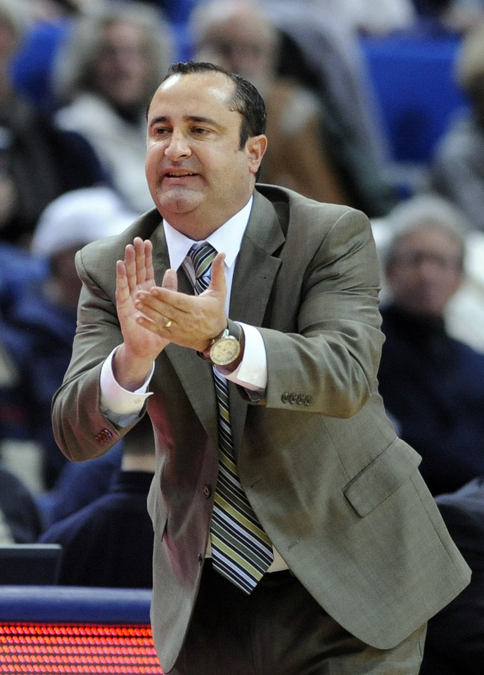 Photo - South Florida head coach Jose Fernandez encourages his team during the second half of their 81-53 loss to Connecticut in an NCAA college basketball game in Hartford, Conn., Sunday, Jan. 26, 2014. (AP Photo/Fred Beckham)