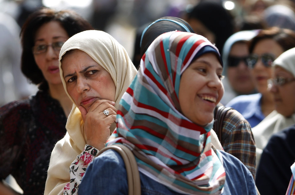 Photo -   Egyptian women wait to vote at Ibn Nafis Language School polling station in Nasr City, Cairo, Egypt, Wednesday, May 23, 2012. More than 15 months after autocratic leader Hosni Mubarak's ouster, Egyptians streamed to polling stations Wednesday to freely choose a president for the first time in generations. Waiting hours in line, some debated to the last minute over their vote in a historic election pitting old regime figures against ascending Islamists.(AP Photo/Fredrik Persson)