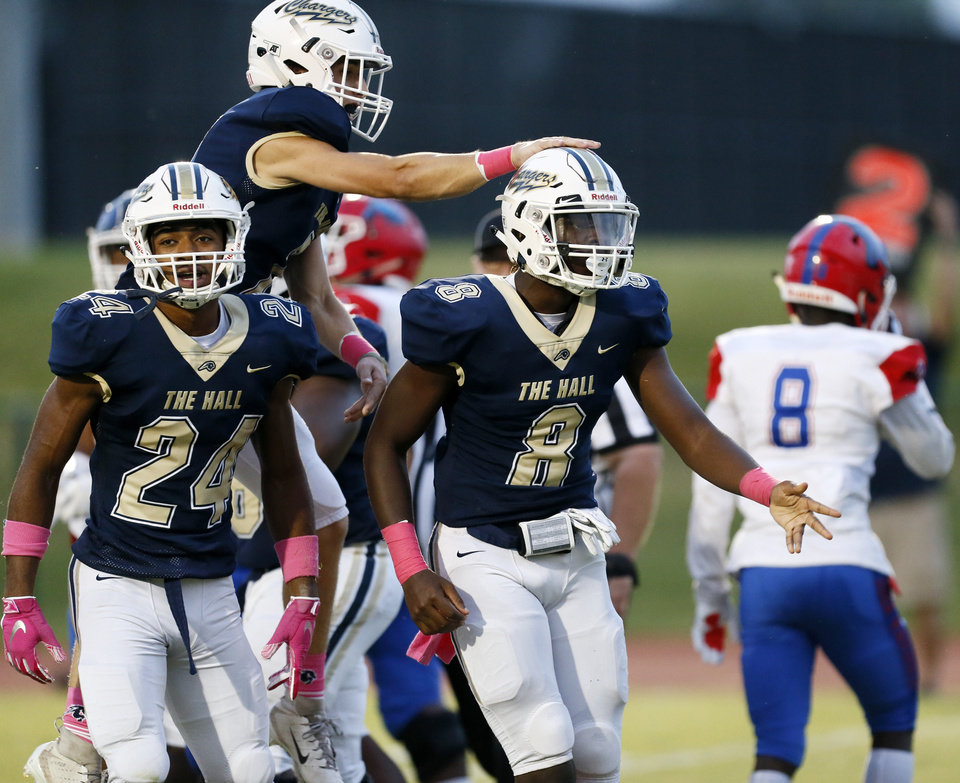 Photo - Heritage Hall's Robert Mbroh (8) gets a slap on the helmet from River Faulkner (7) next to Phillip Smitherman (24) after Mbroh scored a touchdown against John Marshall during a high school football game at Heritage Hall in Oklahoma City, Friday, Oct. 4, 2019. [Nate Billings/The Oklahoman]