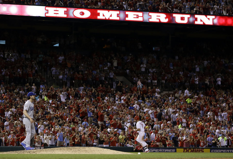Photo - St. Louis Cardinals' Matt Holliday, right, rounds the bases after hitting a two-run home run off Los Angeles Dodgers starting pitcher Dan Haren, left, during the fifth inning of a baseball game Friday, July 18, 2014, in St. Louis. (AP Photo/Jeff Roberson)