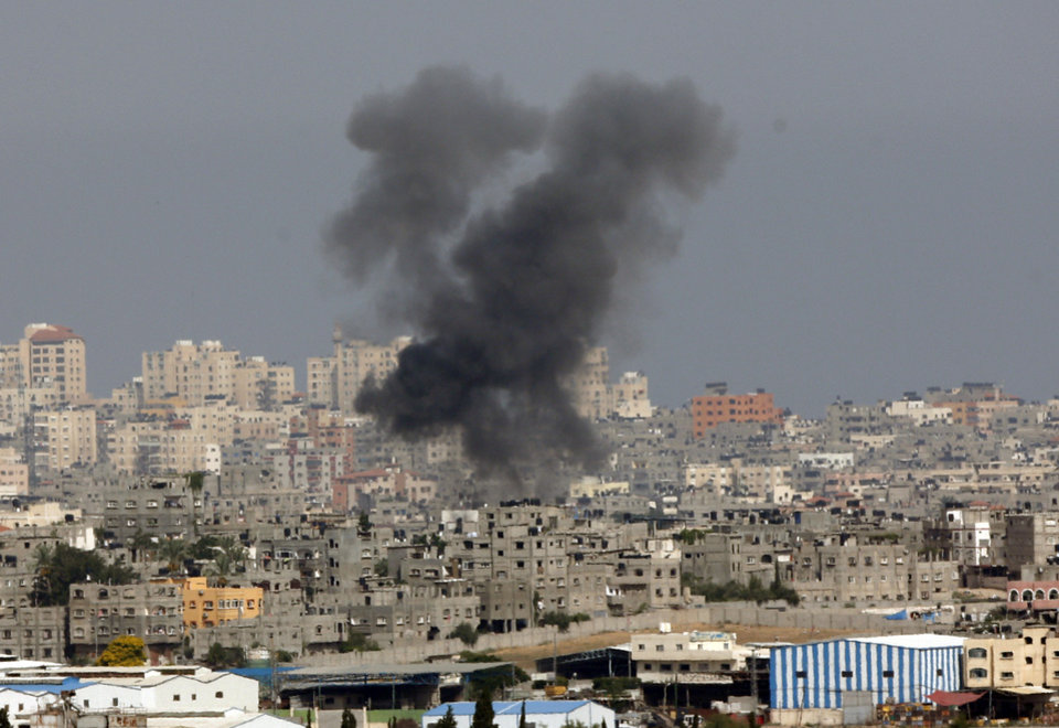 Photo - Smoke rises following an Israeli strike on Gaza, seen from the Israel-Gaza border, Saturday, July 12, 2014. Israeli airstrikes overnight targeting Hamas in Gaza hit a mosque its military says concealed the militant group's weapons, in an offensive that showed no signs of slowing down. Israel launched its campaign five days ago to stop relentless rocket fire on its citizens. While there have been no fatalities in Israel, Palestinian officials said overnight attacks raised the death toll there to over 120, with more than 920 wounded. (AP Photo/Lefteris Pitarakis)
