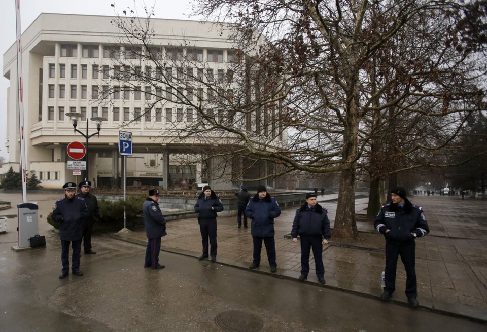 Photo - Ukrainian police officers guard street in front of a local government building in Simferopol, Crimea, Ukraine, Thursday, Feb. 27, 2014. Ukraine put its police on high alert after dozens of armed pro-Russia men stormed and seized local government buildings in Ukraine's Crimea region early Thursday and raised a Russian flag over a barricade. (AP Photo/Darko Vojinovic)