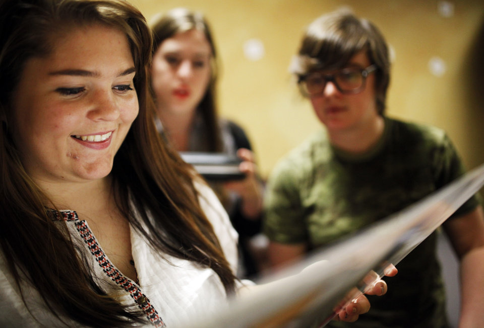 Photo - NewsOK interns (left-right) Jessica Allison, Catherine Sweeney and Paighten Harkins read a clue on the back of piece of paper at Escape OKC on July 11, 2014 in Oklahoma City. Photo by KT King, The Oklahoman