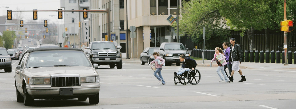 Photo - A woman in a wheelchair and children hurry to cross Hudson Avenue between the Oklahoma County Courthouse and City Hall on Thursday. The six-lane street with 12-foot-wide lanes — highway standard — gets the worst grade from consultant Jeff Speck on walkability.  Photo By Jim Beckel, The Oklahoman