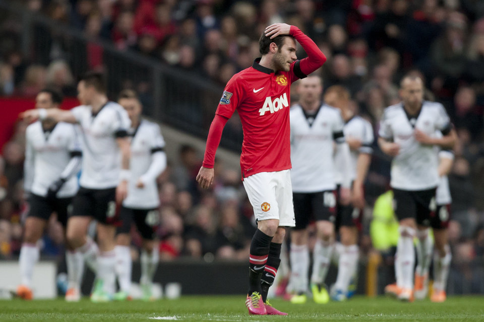 Photo - Manchester United's Juan Mata wipes his hair as Fulham players celebrate their first goal, scored by Steve Sidwell, during their English Premier League soccer match at Old Trafford Stadium, Manchester, England, Sunday Feb. 9, 2014. (AP Photo/Jon Super)