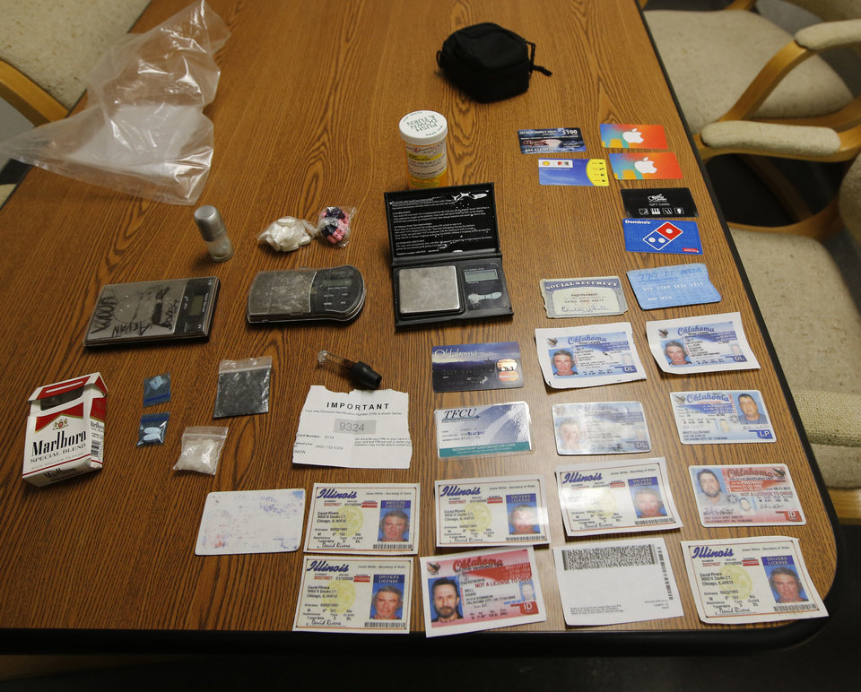 Photo -  Oklahoma County sheriff's office warrant team members seized fake identification cards, drugs and paraphernalia during an arrest in Bethany. [Photo by Steve Gooch, The Oklahoman]