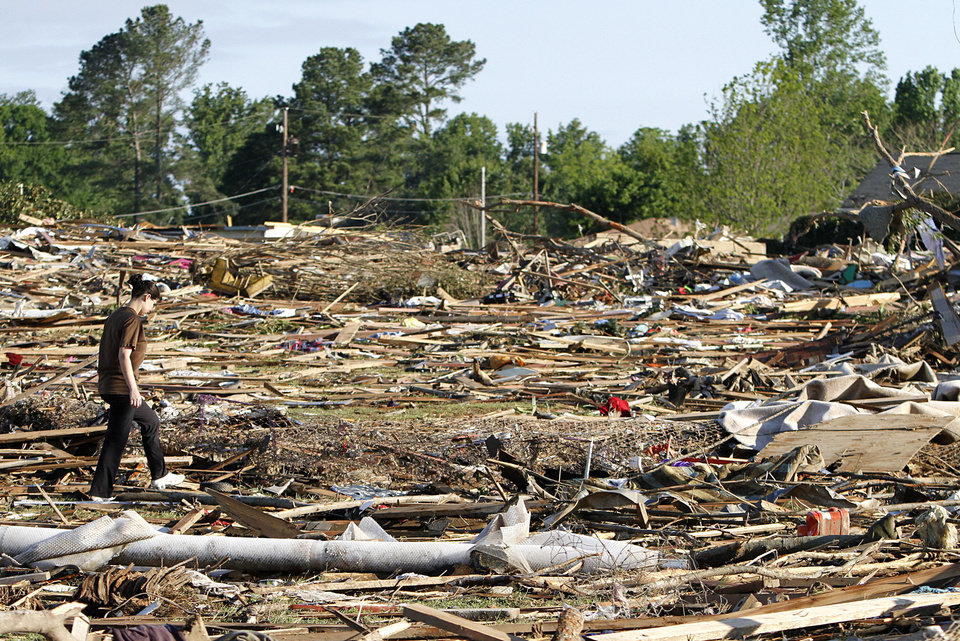 Photo - Tiffany Wood walks through her backyard looking for belongings Thursday, April 28, 2011 after a tornado hit Pleasant Grove just west of downtown Birmingham, Ala., Wednesday afternoon. (AP Photo/Butch Dill)