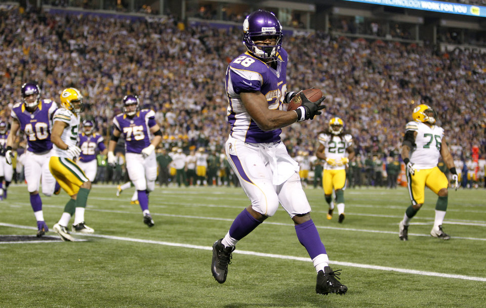 Photo - Minnesota Vikings running back Adrian Peterson catches a two-yard touchdown pass during the second half of an NFL football game against the Green Bay Packers Sunday, Dec. 30, 2012, in Minneapolis. (AP Photo/Genevieve Ross)