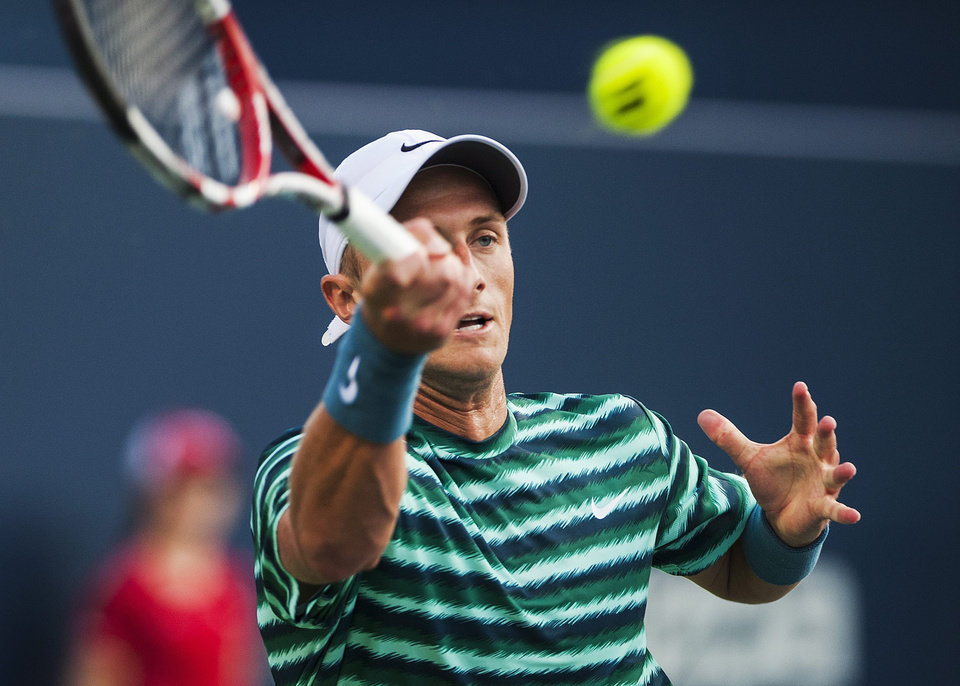 Photo - Canada's Peter Polansky returns the ball against Roger Federer, of Switzerland, during the Rogers Cup men's tennis tournament in Toronto on Tuesday, Aug. 5, 2014. (AP Photo/The Canadian Press, Aaron Vincent Elkaim)