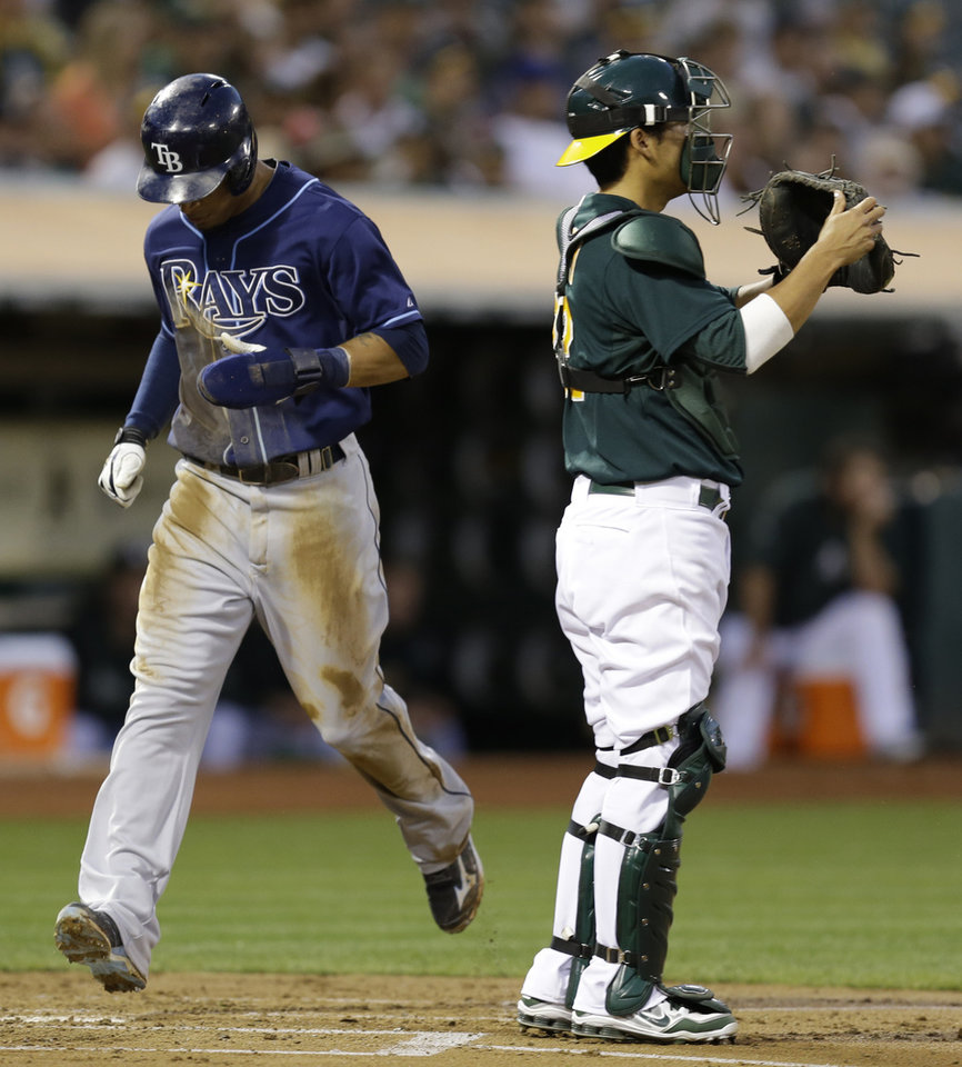 Photo - Tampa Bay Rays' Desmond Jennings, left, scores past Oakland Athletics catcher Kurt Suzuki in the second inning of a baseball game, Friday, Aug. 30, 2013, in Oakland, Calif. Jennings scored on a single by Yunel Escobar. (AP Photo/Ben Margot)