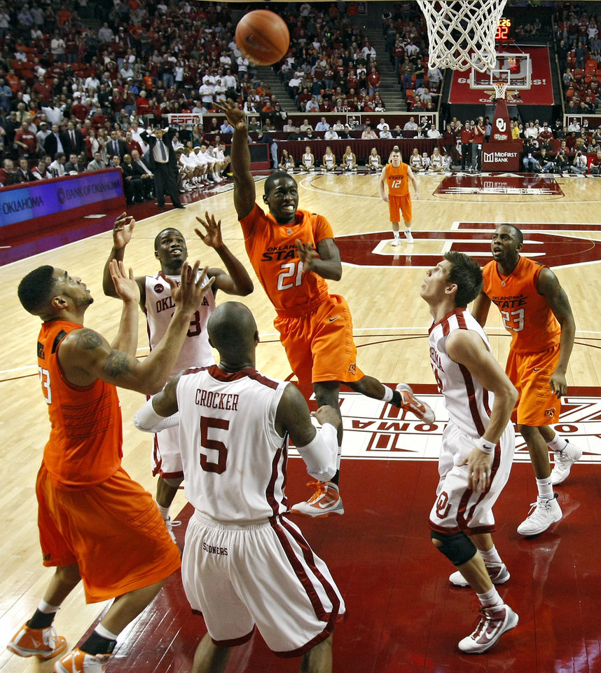 Photo - OSU's Fred Gulley (21) puts up a shot over the OU defense during the second half of the college bedlam basketball game between The University of Oklahoma Sooners (OU) and Oklahoma State University University Cowboys (OSU) at the Lloyd Noble Center on Monday, Jan. 11, 2010, in Norman, Okla.