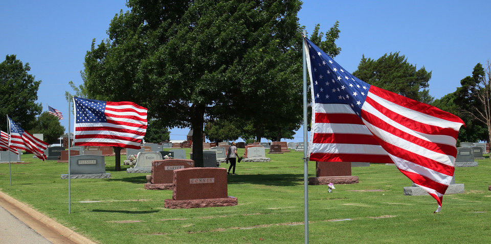 Photo -  BELOW: American flags are posted along a road at Memorial Park Cemetery.
