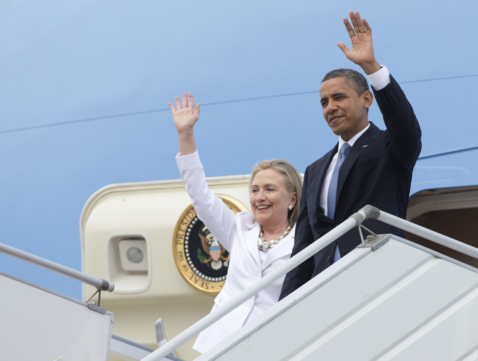 Photo -   U.S. President Barack Obama and Secretary of State Hillary Rodham Clinton wave as they arrive at Yangon International Airport in Yangon, Myanmar, on Air Force One, Monday, Nov. 19, 2012. This is the first visit to Myanmar by a sitting U.S. president. (AP Photo/Carolyn Kaster)