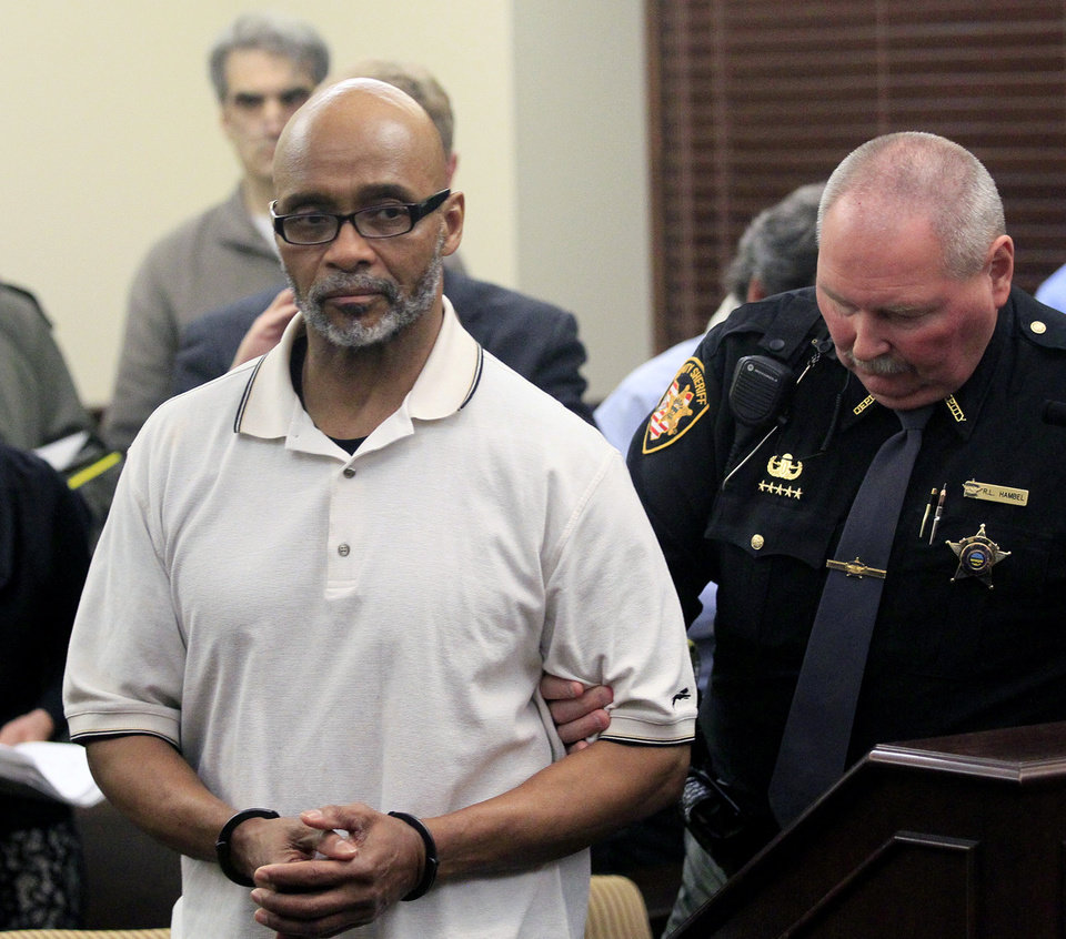 Photo - Douglas Prade is taken into custody at the Summit County Courthouse, Thursday, March 20, 2014, in Akron, Ohio. A judge ordered Prade to appear in court Thursday so she could decide whether he should be sent back to prison or remain free while he appeals. Prade could head back to prison after being exonerated in his ex-wife's killing, he served 15 years. (AP Photo/Akron Beacon Journal, Karen Schiely)  MANDATORY CREDIT