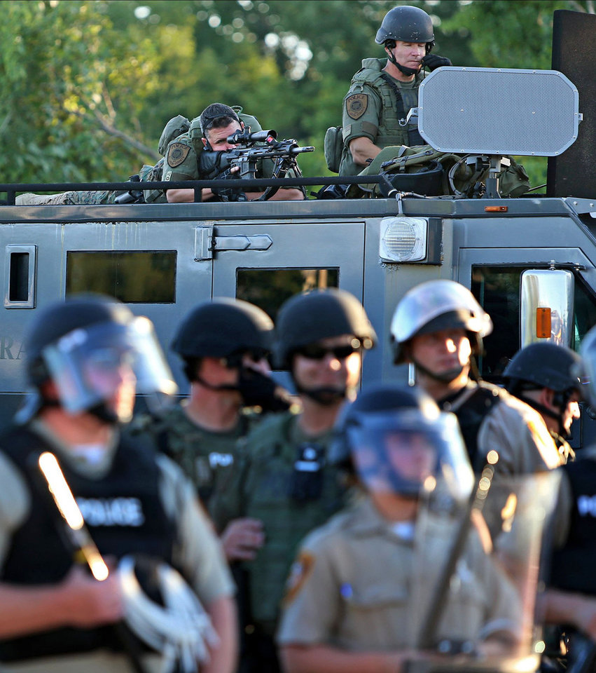 Photo - A police sharp shooter keeps an eye on protesters along W. Florissant Avenue on Tuesday, Aug. 12, 2014 near the QuikTrip that was burned down a few days earlier in Ferguson. (AP Photo/St. Louis Post-Dispatch, David Carson)