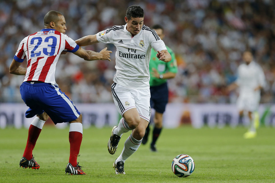 Photo - Real Madrid's James Rodriguez from Colombia, fights for the ball with Atletico Madrid's Joao Miranda from Brazil, left, during a Spanish Super Cup soccer match at Santiago Bernabeu stadium  in Madrid, Spain, Tuesday, Aug. 19, 2014 . (AP Photo/Daniel Ochoa de Olza)