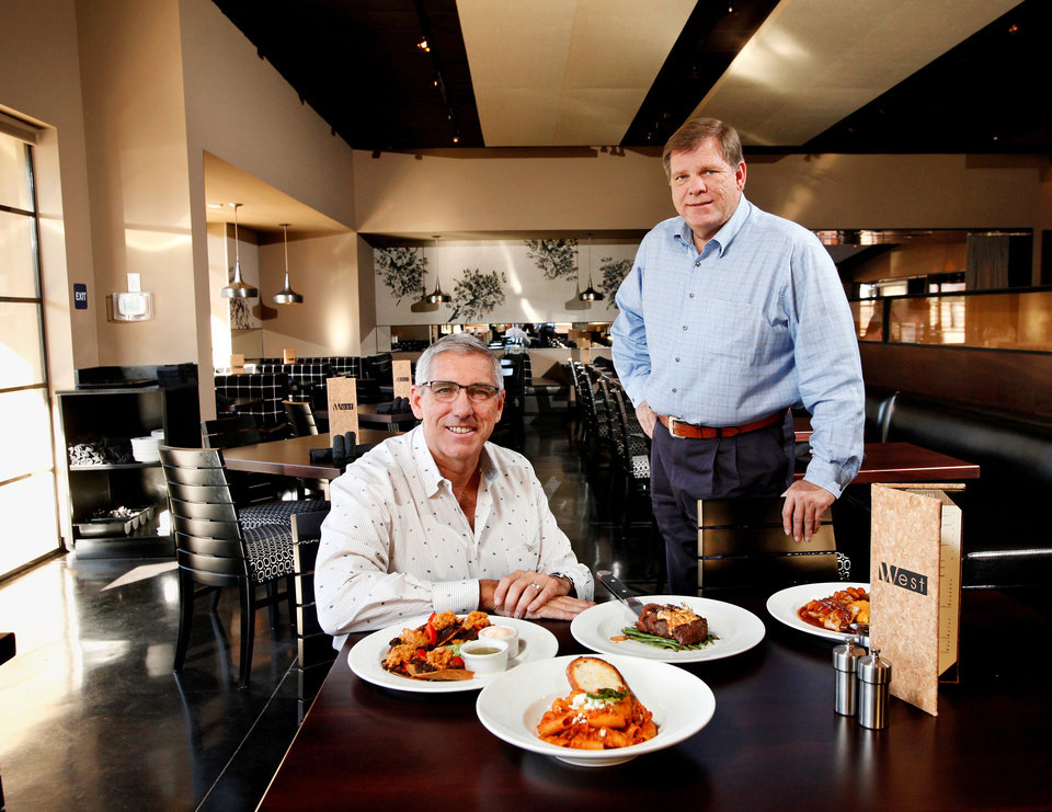 Photo -  Rick Haynes, seated, and older brother David Haynes, with some of the featured menu items at their new restaurant,  West, 6714 N. Western, in northwest Oklahoma City.   Photo by Jim Beckel, The Oklahoman