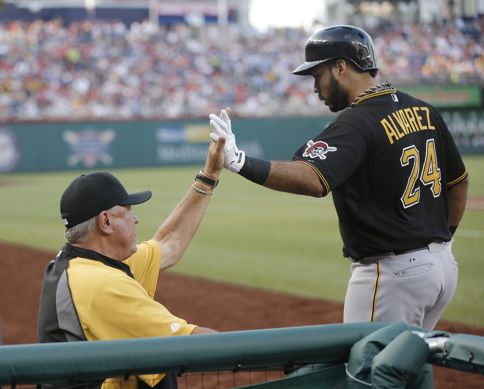 Photo - Pittsburgh Pirates' Pedro Alvarez (24), is greeted in the dugout by manager Clint Hurdle, left, after hitting a solo home run off Washington Nationals starting pitcher Stephen Strasburg during the second inning of a baseball game at Nationals Park, Wednesday, July 24, 2013, in Washington. (AP Photo/Pablo Martinez Monsivais)