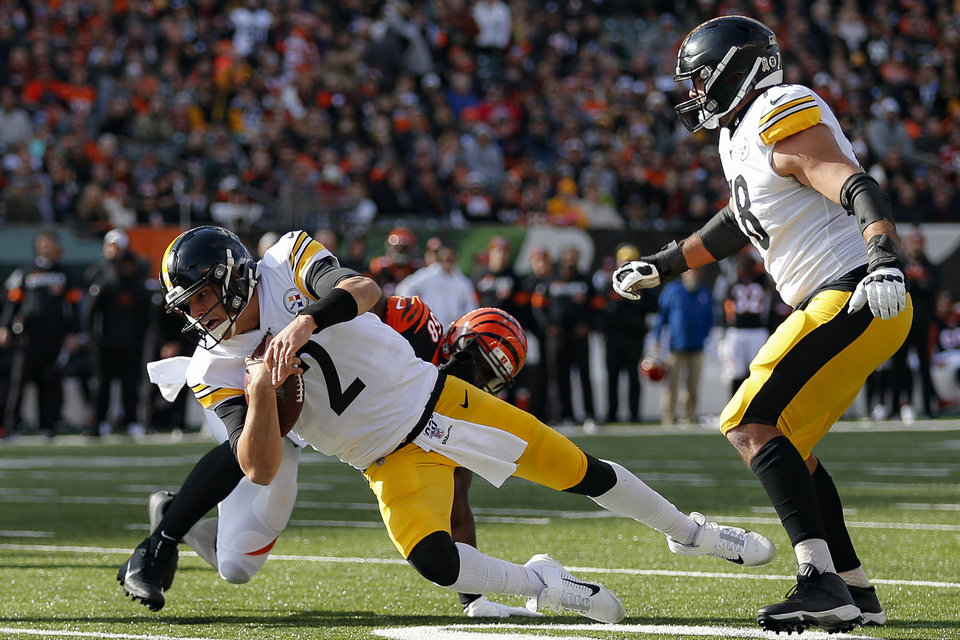 Photo - Pittsburgh Steelers quarterback Mason Rudolph (2) grounds the ball under pressure from Cincinnati Bengals defensive end Carl Lawson (58) during the first half an NFL football game, Sunday, Nov. 24, 2019, in Cincinnati. (AP Photo/Gary Landers)