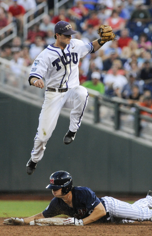 Photo - Mississippi's Auston Bousfield, bottom, steals second base as TCU shortstop Keaton Jones leaps for the ball, in the fifth inning of an NCAA baseball College World Series elimination game in Omaha, Neb., Thursday, June 19, 2014. (AP Photo/Eric Francis)