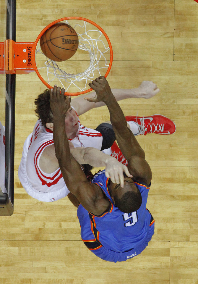 Oklahoma City's Serge Ibaka (9) dunks over Houston's Omer Asik (3) during Game 3 in the first round of the NBA playoffs between the Oklahoma City Thunder and the Houston Rockets at the Toyota Center in Houston, Texas, Sat., April 27, 2013. Oklahoma City won 104-101. Photo by Bryan Terry, The Oklahoman