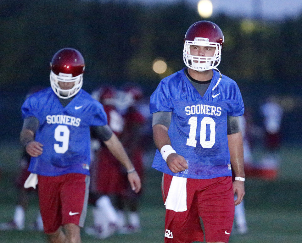 Photo - Oklahoma University quarterbacks Blake Bell, right,  and Trevor Knight  warm up at a preseason NCAA college football practice in Norman, Okla. on Friday, Aug.  2, 2013.  (AP Photo/Tulsa World,  Matt Barnard)  ONLINE OUT; TV OUT; TULSA OUT  ORG XMIT: OKTUL101
