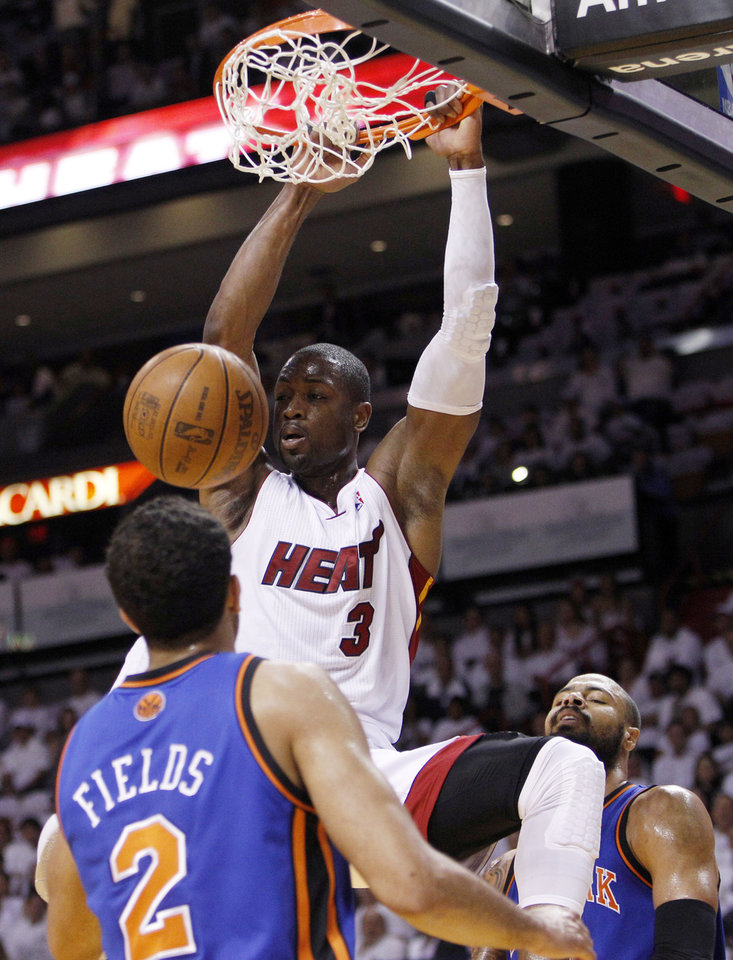 Photo -   Miami Heat's Dwyane Wade (3) dunks in front of New York Knicks' Landry Fields (2) and Tyson Chandler, right, in the first half of an NBA basketball game in the first round of the Eastern Conference playoffs in Miami, Monday, April 30, 2012. (AP Photo/Lynne Sladky)