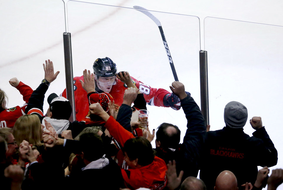 Photo - Chicago Blackhawks right wing Marian Hossa, of Slovakia, celebrates along the boards with fans after scoring the winning goal during overtime of an NHL hockey game against the Edmonton Oilers, Monday, Feb. 25, 2013, in Chicago. The Blackhawks won 3-2. (AP Photo/Charles Rex Arbogast)