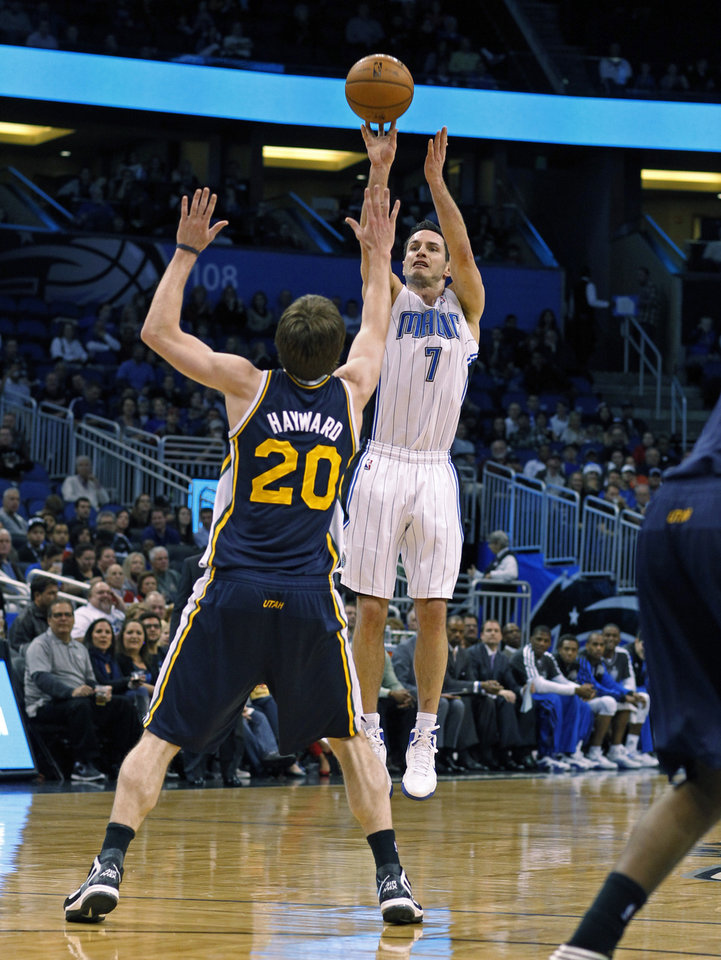 Orlando Magic guard J.J. Redick (7) releases a 3-point shot over Utah Jazz guard Gordon Hayward (20) during the first half of an NBA basketball game, Sunday, Dec. 23, 2012, in Orlando, Fla. (AP Photo/Scott Iskowitz)