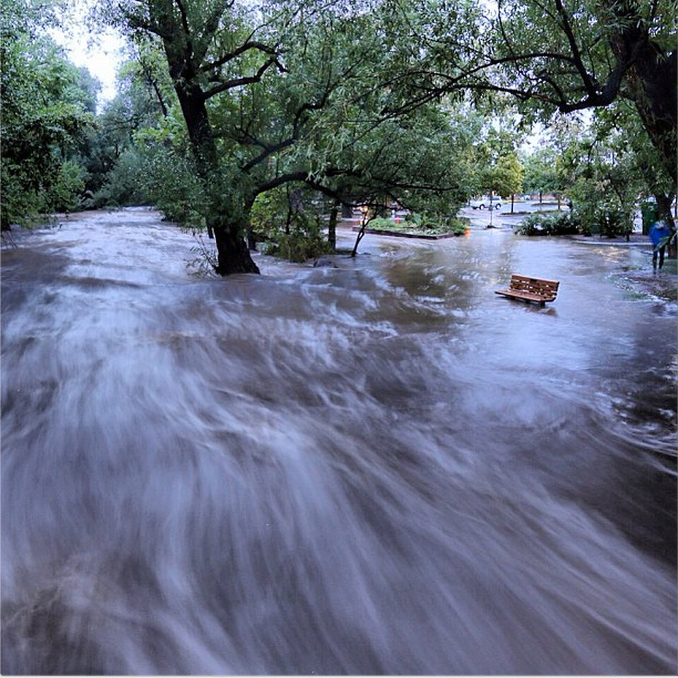 Photo - In this image made with a slow shutter speed which blurred the rushing water, flood waters course through a small park in Boulder, Colo., Thursday morning, Sept. 12, 2013. Heavy rains and scarring from recent wildfires sent walls of water crashing down mountainsides in the area. (AP Photo/Jud Valeski)