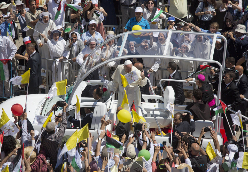 Photo - Pope Francis greets people as he arrives to the West Bank town of Bethlehem, Sunday May 25, 2014. Pope Francis is paying a three day visit to Jordan, West Bank and Israel.(AP Photo/Dusan Vranic)
