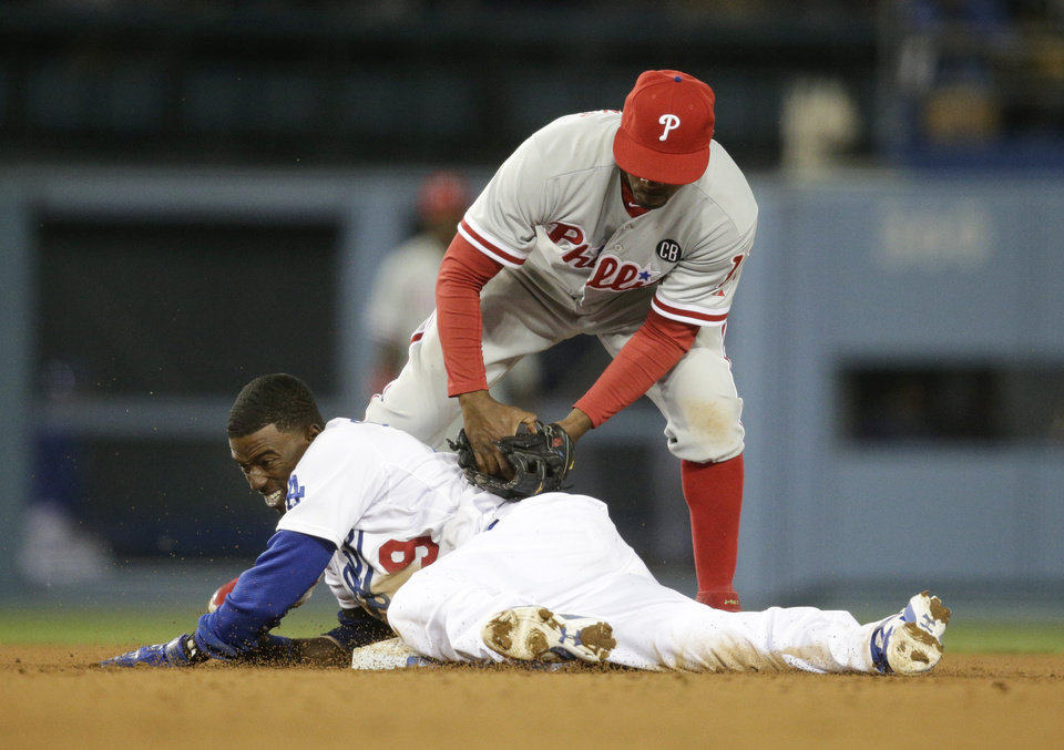 Photo - Los Angeles Dodgers' Dee Gordon, bottom, takes second base against Philadelphia Phillies shortstop Jimmy Rollins after hitting a double during the seventh inning of a baseball game on Tuesday, April 22, 2014, in Los Angeles. (AP Photo/Jae C. Hong)