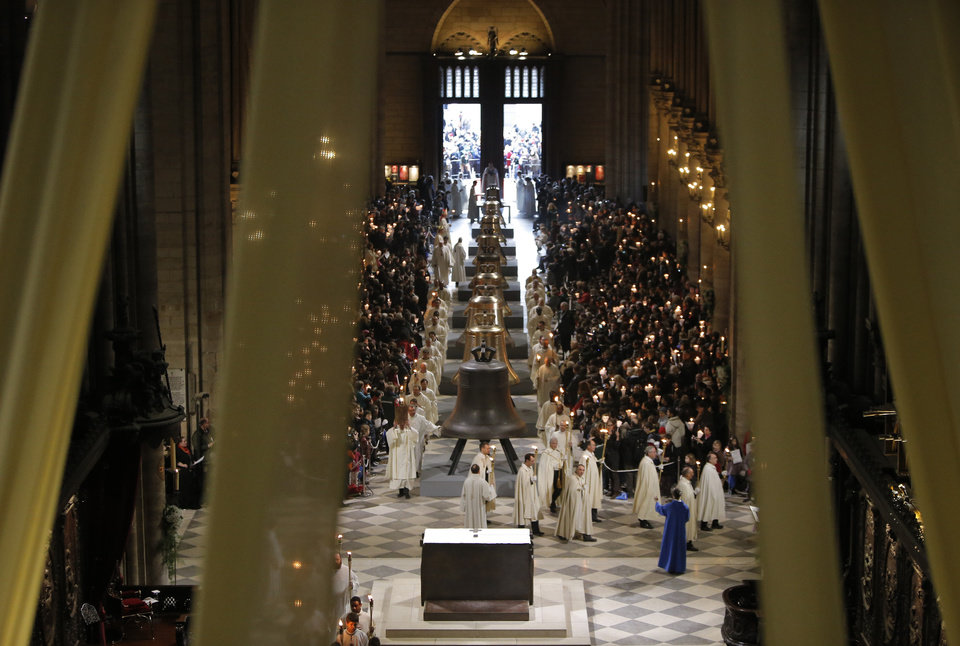 Photo - The nine new bronze bells are displayed in Notre Dame cathedral during a ceremony of blessing by Paris Archbishop Andre Vingt-Trois in Paris, Saturday, Feb. 2, 2013. Nine enormous new bronze bells have made their way at Notre Dame Cathedral, helping the medieval edifice to rediscover its historical harmony. (AP Photo/Francois Mori)