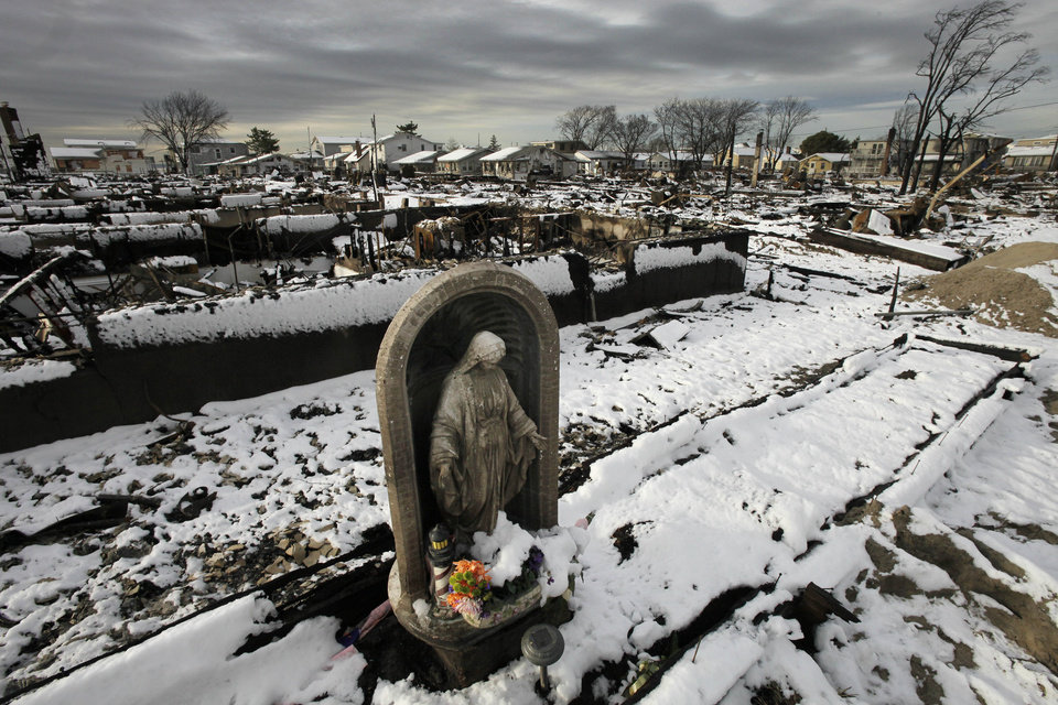 Photo -   A religious statue stands in the fire-scorched landscape of Breezy Point after a Nor'easter snow, Thursday, Nov. 8, 2012 in New York. The beachfront neighborhood was devastated during Superstorm Sandy when a fire pushed by the raging winds destroyed many homes. (AP Photo/Mark Lennihan)