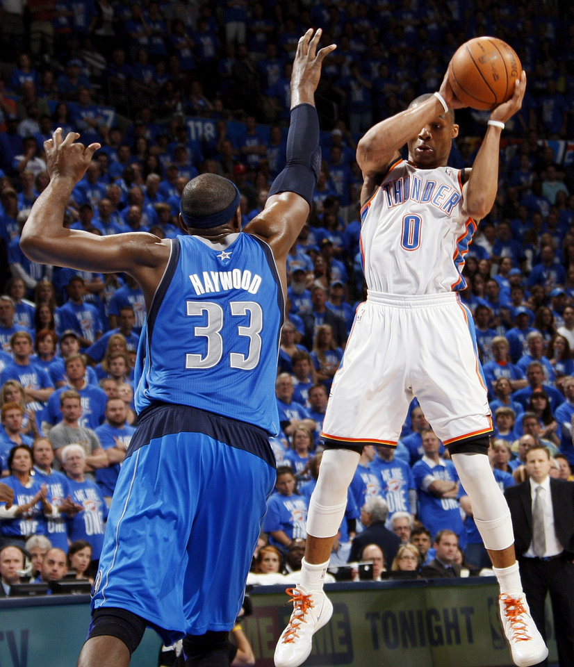 Oklahoma City\'s Russell Westbrook (0) passes the ball away from Dallas\' Brendan Haywood (33) during game one of the first round in the NBA playoffs between the Oklahoma City Thunder and the Dallas Mavericks at Chesapeake Energy Arena in Oklahoma City, Saturday, April 28, 2012. Oklahoma City won, 99-98. Photo by Nate Billings, The Oklahoman