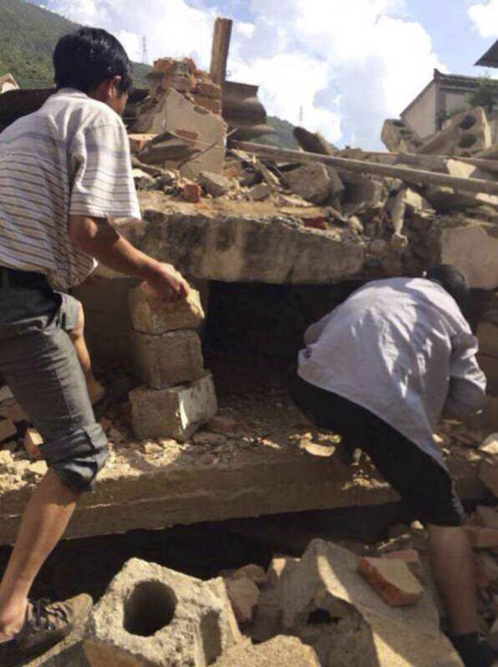 Photo - In this photo taken by cellphone and released by China's Xinhua News Agency, men at rubbles of buildings look for survivors after an earthquake in Ludian County of Zhaotong City in southwest China's Yunnan Province Sunday, Aug. 3, 2014. A strong earthquake rattled southwest China on Sunday, knocking out communication and power lines and causing people to rush out of buildings, but there were no immediate reports of injuries. (AP Photo/Xinhua/Hu Chao) NO SALES