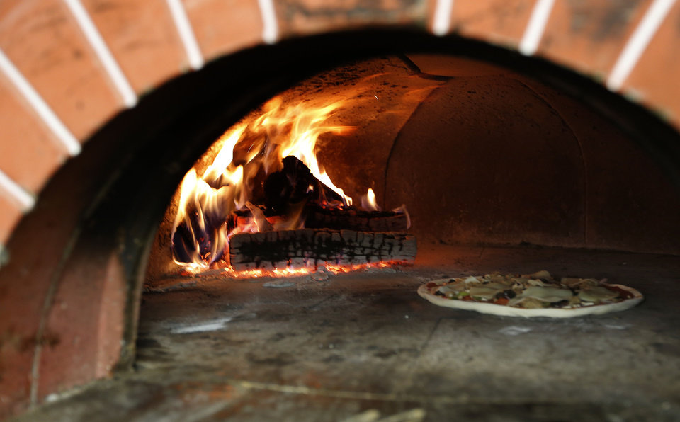 Photo -  A pizza cooks in a wood-burning stove at Gabriella's Italian Grill and Pizzeria in the old County Line building on 1226 NE 63 in Oklahoma City, Friday, July 13, 2012. Photo by Sarah Phipps, The Oklahoman.  SARAH PHIPPS - SARAH PHIPPS