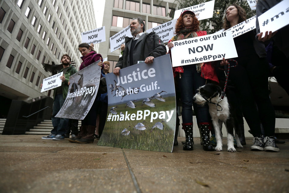 Photo - Protestors from the National Audubon Institute, the Gulf Restoration Network and other organizations stand outside Federal Court on the first day of the Gulf oil spill settlement trial in New Orleans, Monday, Feb. 25, 2013. U.S. District Judge Carl Barbier is scheduled to hear several hours of opening statements Monday by lawyers for the companies, federal and state governments and others who sued over the disaster. Barbier is hearing the case without a jury. (AP Photo/Gerald Herbert)