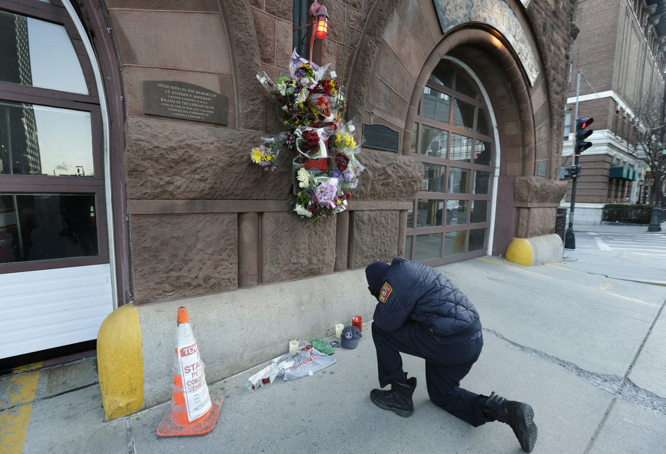 Photo - Somerville, Mass. firefighter Earl Johnson kneels to pray in front of a makeshift memorial on the front of fire station Engine 33, Thursday, March 27, 2014, in Boston. Fire station Engine 33 was the station of fallen firefighters Lt. Edward J. Walsh and Michael R. Kennedy who lost their lives fighting a 9-alarm fire in a four-story brownstone in Boston's Back Bay neighborhood Wednesday, March 26, 2014. (AP Photo/Steven Senne)